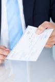 Geschäftsmann Holding Cheque Lizenzfreie Stockbilder