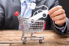 Geschäftsmann-Holding Electric Paper-Auto über Warenkorb stockbild