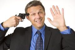Geschäftsmann-Holding-Gewehr zu seinem Kopf beim Lächeln Stockfoto