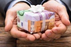 Geschäftsmann Holding Gift Box gemacht von Euro-Papernotes stockfotos