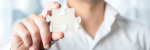 Geschäftsmann-Holding Jigsaw Puzzle-Stück Lizenzfreie Stockfotos