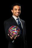 Geschäftsmann-Holding-Kugel mit Weltmarkierungsfahnen Lizenzfreies Stockfoto