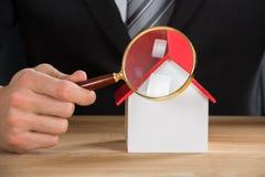 Geschäftsmann Holding Magnifying Glass auf Haus-Modell Lizenzfreies Stockbild