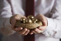 Geschäftsmann Holding Nest Full von goldenen Eiern Lizenzfreies Stockbild