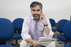 Geschäftsmann Holding Newspaper While beim Anruf Lizenzfreie Stockfotografie