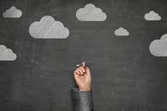 Geschäftsmann Holding Paper Plane unter den Wolken gezeichnet auf Tafel stockbilder