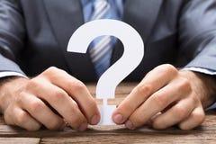 Geschäftsmann Holding Paper Question Mark At Table stockbilder