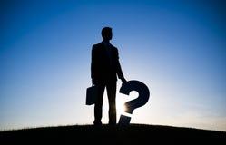 Geschäftsmann-Holding Questions-Kennzeichen Lizenzfreie Stockbilder