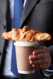 Geschäftsmann Holding Takeaway Coffee und Hörnchen Stockbild