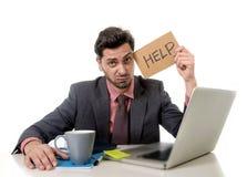 Geschäftsmann im Anzug und Bindung, die am Schreibtisch arbeitet auf Computerlaptop bitten um die Hilfe hält Pappzeichen sitzt Stockbilder