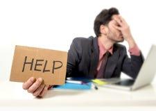 Geschäftsmann im Anzug und Bindung, die am Schreibtisch arbeitet auf Computerlaptop bitten um die Hilfe hält Pappzeichen sitzt Lizenzfreie Stockfotos