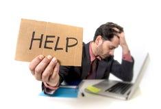 Geschäftsmann im Anzug und Bindung, die am Schreibtisch arbeitet auf Computerlaptop bitten um die Hilfe hält Pappzeichen sitzt Stockfotografie