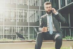 Geschäftsmann im Anzug und in der Bindung sitzt draußen auf Bank, trinkender Kaffee und spricht an seinem Handy Ist in der Nähe L stockfotografie