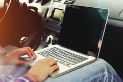 Geschäftsmann im Auto arbeitet an einem Laptop Lizenzfreie Stockbilder