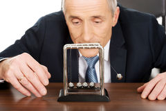 Geschäftsmann im Büro, das mit Newtonbällen spielt Lizenzfreies Stockfoto