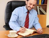 Geschäftsmann im Büro, das an seinem Arbeitsplatz arbeitet Lizenzfreie Stockfotos