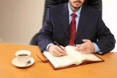 Geschäftsmann im Büro, das an seinem Arbeitsplatz arbeitet. Lizenzfreie Stockfotografie