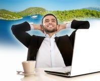 Geschäftsmann im Büro denkend und von den Sommerferien träumend Lizenzfreie Stockfotos