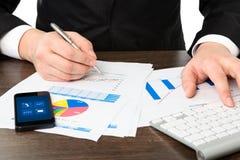 Geschäftsmann im Büro der Tabelle mit Grafiken und Telefon Lizenzfreies Stockfoto