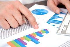 Geschäftsmann im Büro der Tabelle zeigt auf die Grafiken Stockfotografie