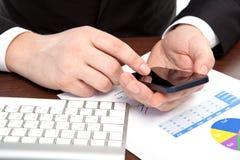 Geschäftsmann im Büro mit den Grafiken, die ein Telefon halten Stockfoto