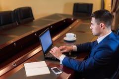 Geschäftsmann im Büro mit Laptop Stockbilder