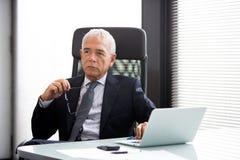 Geschäftsmann im Büro mit Laptop-Computer Lizenzfreie Stockfotos