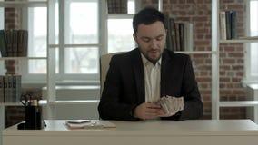 Geschäftsmann im Büro sein Geld genießend stock footage