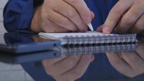 Geschäftsmann im Büro unter Verwendung des Taschenbuches für das Schreiben von Informationen lizenzfreies stockbild