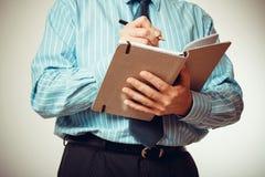 Geschäftsmann im blauen Hemd mit Notizbuch Stockbilder