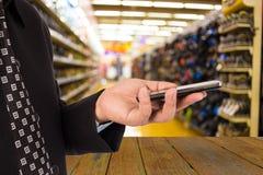 Geschäftsmann im Einkaufszentrum unter Verwendung des Handys Lizenzfreies Stockbild