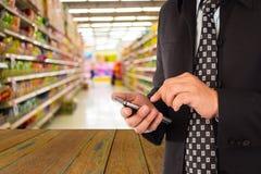 Geschäftsmann im Einkaufszentrum unter Verwendung des Handys Lizenzfreie Stockfotos