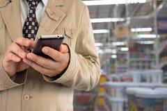 Geschäftsmann im Einkaufszentrum unter Verwendung des Handys Lizenzfreies Stockfoto
