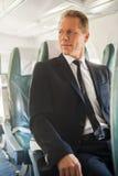 Geschäftsmann im Flugzeug Stockfotografie