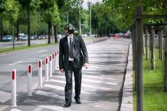 Geschäftsmann im Freien, eine Gasmaske tragend, die zum Himmel schaut stockfoto