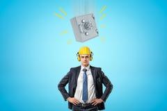 Geschäftsmann im gelben Schutzhelm mit Gehörschutzkapseln, stehend mit den Händen auf Hüften und dem großen schweren Geldsafe, da stockbilder