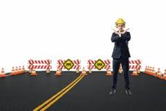 Geschäftsmann im gelben Sturzhelm und die Kopfhörer, die auf der Straße im Bau mit seinen Armen stehen, kreuzten im Halt Lizenzfreie Stockbilder