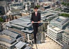 Geschäftsmann im Gleichgewicht auf einem Seil über einer Stadt stockbilder