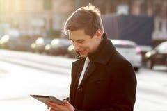 Geschäftsmann im Mantel unter Verwendung der Tablette Stockbilder