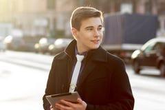 Geschäftsmann im Mantel unter Verwendung der Tablette Lizenzfreie Stockfotografie