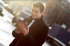 Geschäftsmann im Mantel unter Verwendung der Tablette Stockfoto