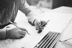 Geschäftsmann im modernen Büro Simsender Mitteilungssmartphone und -c$halten von Bleistifthänden Generische Designnotizbuch-Holzt Lizenzfreie Stockbilder