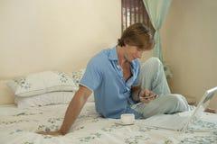 Geschäftsmann im Schlafzimmer mit Handy Stockfoto