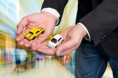 Geschäftsmann im schwarzen Anzug, der zwei kleine Automodelle hält Lizenzfreie Stockfotos