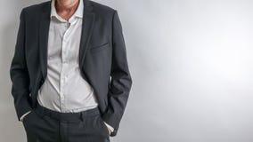 Geschäftsmann im schwarzen Anzug haben seine Hände in seinen Taschen lizenzfreie stockfotografie