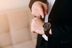 Geschäftsmann im schwarzen Anzugsblick auf seine teure Schweizer Armbanduhr auf seiner Hand und dem Aufpassen der Zeit Stockbilder