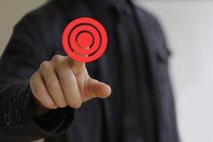 Geschäftsmann im schwarzen Drücken auf rotes Zielziel Stockfotografie