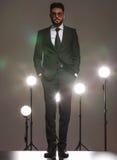 Geschäftsmann im Schwarzen, stehend im Studio mit den Händen in den Taschen Stockbild