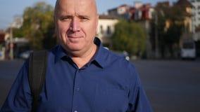 Geschäftsmann im Straßen-Text mit Mobiltelefon-Blick zur Kamera und dem Lächeln überzeugt stock footage