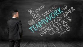 Geschäftsmann im vollen Wachstum, das schwarze Wand mit Skizzen der Teamwork-Bildung betrachtet Lizenzfreie Stockbilder